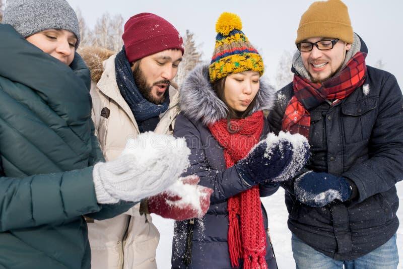 Amigos jovenes que juegan con nieve imagen de archivo libre de regalías