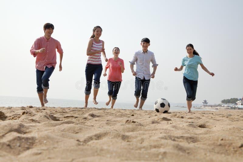 Amigos jovenes que juegan a fútbol en la playa imagen de archivo libre de regalías