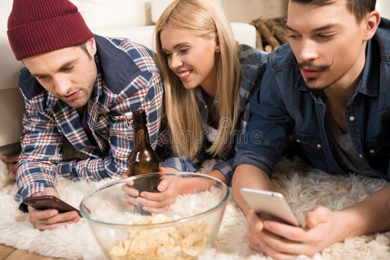Amigos jovenes que mienten en la alfombra y que usan smartphones mientras que bebe la cerveza imagen de archivo libre de regalías