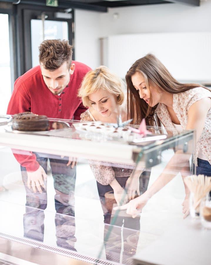 Amigos jovenes que miran el gabinete de exhibición el café imagen de archivo