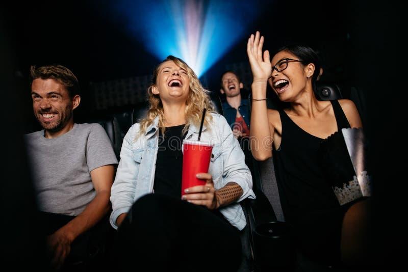 Amigos jovenes que miran película de la comedia en teatro fotografía de archivo