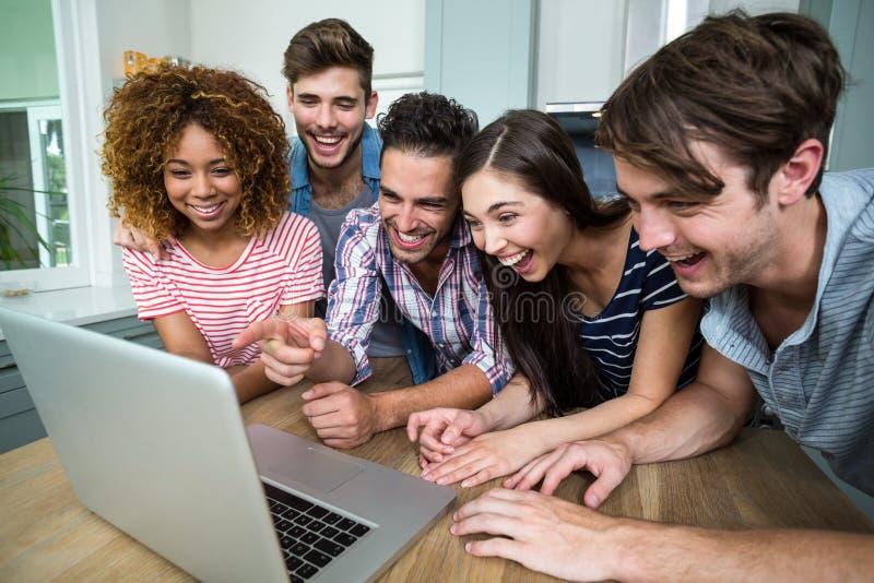 Amigos jovenes que ríen mientras que mira en ordenador portátil en la tabla imagenes de archivo