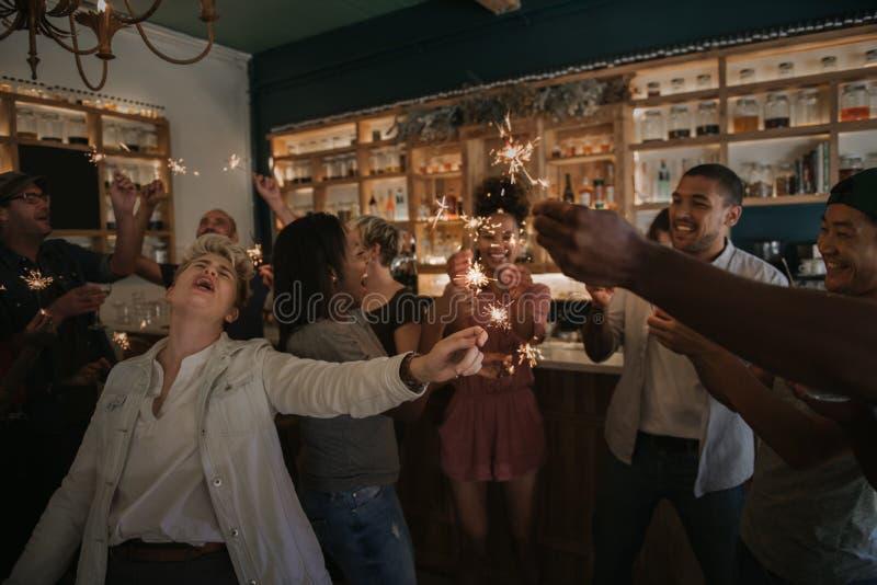 Amigos jovenes que ríen y que celebran con las bengalas en una barra imagen de archivo