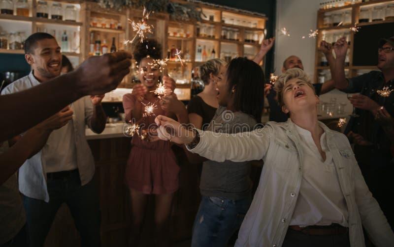 Amigos jovenes que r?en y que celebran con las bengalas en una barra fotografía de archivo libre de regalías