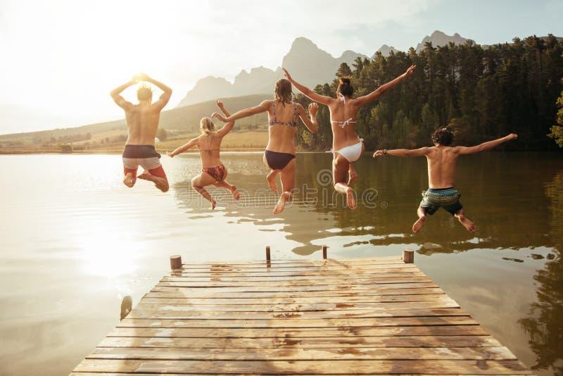 Amigos jovenes que saltan en el lago de un embarcadero imagen de archivo