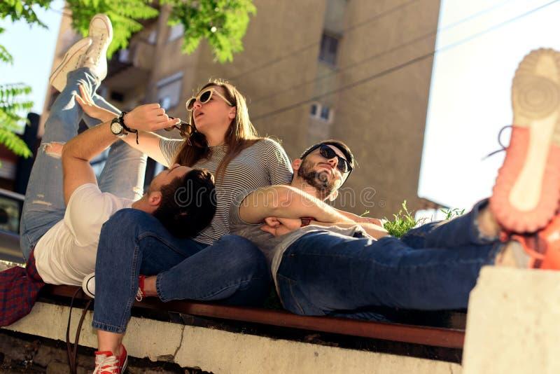 Amigos jovenes que se acuestan en banco del jardín del aire libre imagenes de archivo