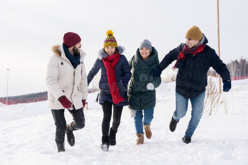 Amigos jovenes que se divierten en invierno imagenes de archivo