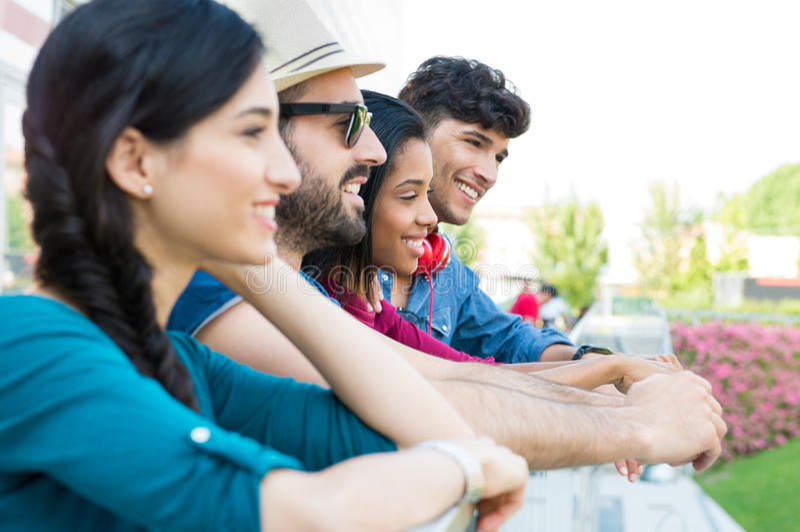 Amigos jovenes que se inclinan en la verja imagenes de archivo