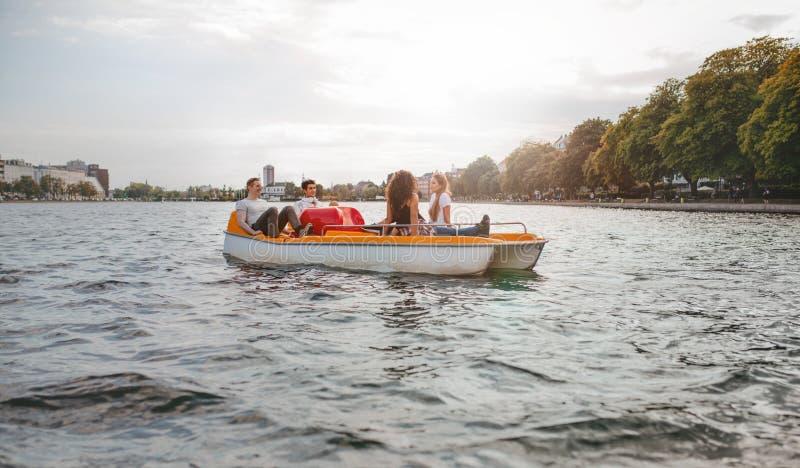 Amigos jovenes que se sientan en el barco del pedal que disfruta de verano foto de archivo