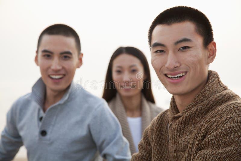 Amigos jovenes que se sientan en la playa fotos de archivo