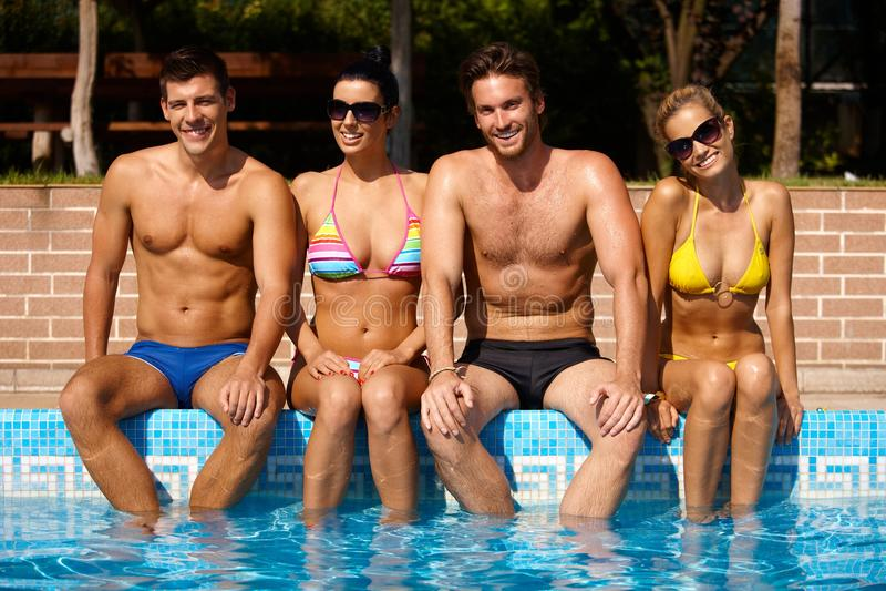 Amigos jovenes que se sientan sonriendo de la piscina fotos de archivo libres de regalías
