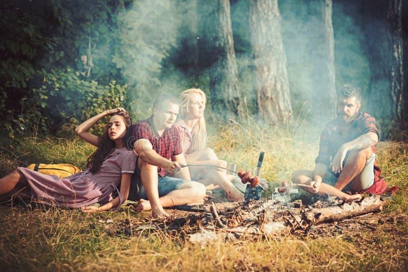 Amigos jovenes que tienen partido de la barbacoa, al aire libre Parrilla deliciosa de la barbacoa con carbón de leña Salchichas e fotos de archivo