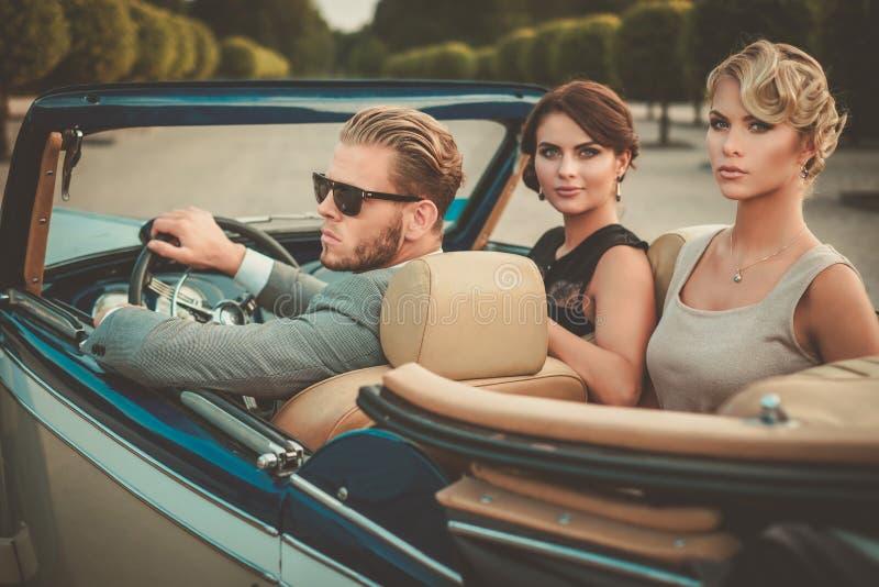 Amigos jovenes ricos en un convertible clásico imagen de archivo libre de regalías