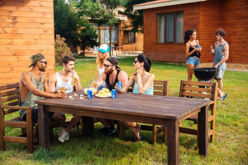 Amigos jovenes sonrientes que se sientan y que hablan en partido al aire libre del verano fotos de archivo