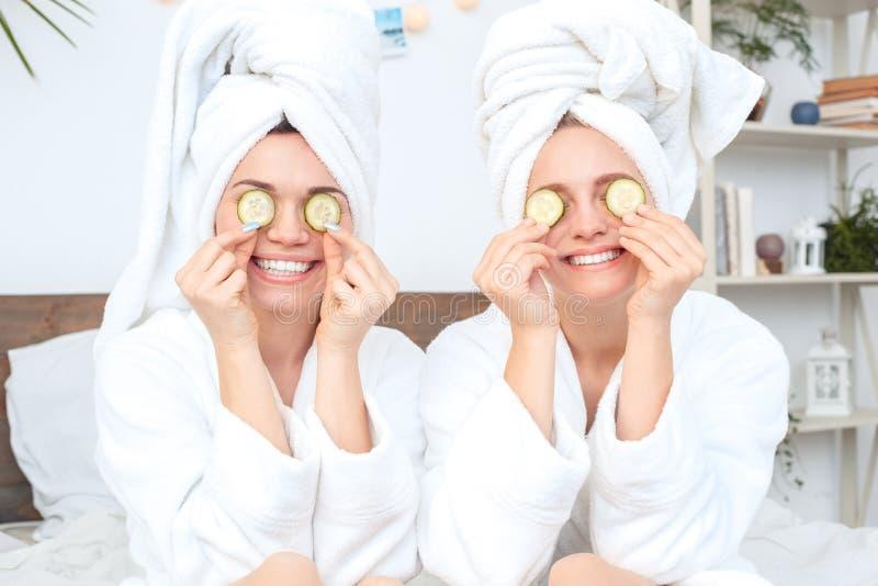 Amigos junto em casa no cuidado da beleza das vestes de banho que senta-se cobrindo os olhos com o sorriso das partes do pepino t fotografia de stock