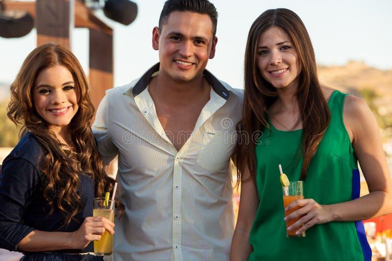 Amigos latinos felices que tienen bebidas imagen de archivo