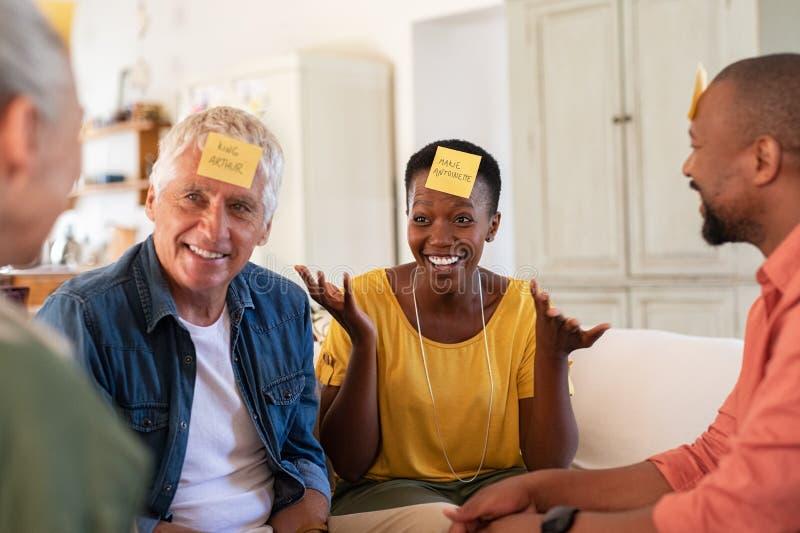 Amigos maduros felices que juegan en casa imagen de archivo libre de regalías