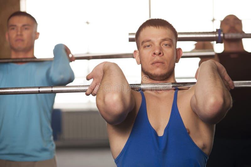 Amigos masculinos aptos que levantan pesas de gimnasia durante la sesión del entrenamiento en gimnasio imagenes de archivo