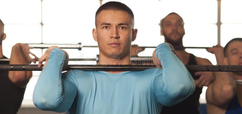 Amigos masculinos aptos que levantan pesas de gimnasia durante la sesi?n del entrenamiento en gimnasio fotografía de archivo