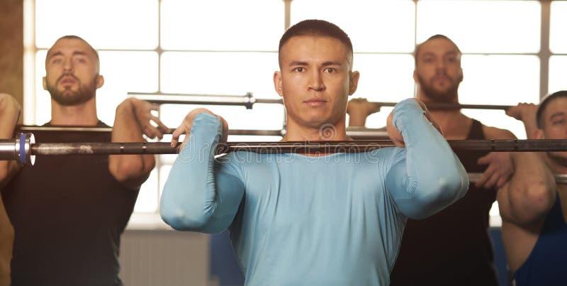 Amigos masculinos aptos que levantan pesas de gimnasia durante la sesi?n del entrenamiento en gimnasio fotos de archivo