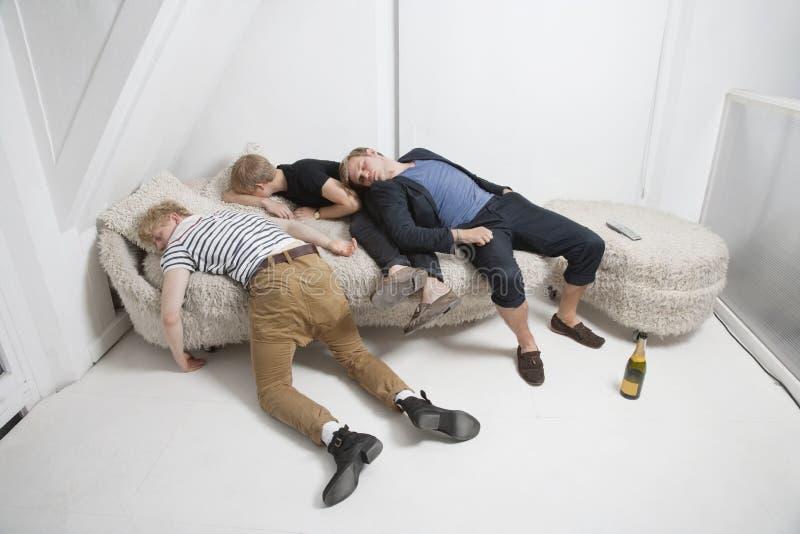 Amigos masculinos bêbados que dormem no sofá da pele após o partido fotografia de stock
