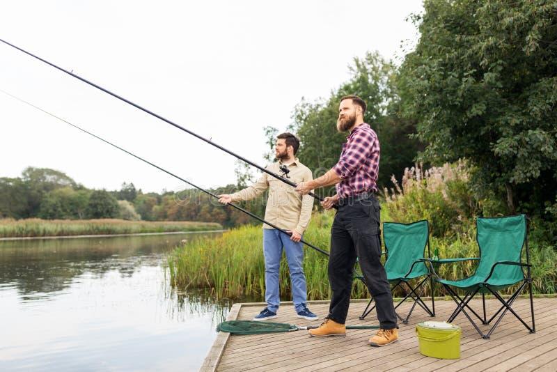 Amigos masculinos com as varas de pesca no cais do lago fotos de stock royalty free