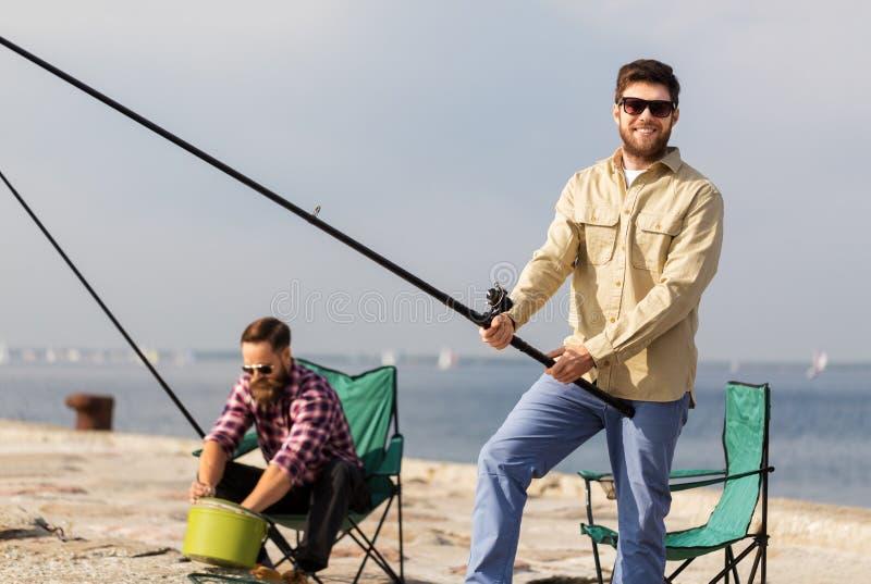 Amigos masculinos com as varas de pesca no cais do mar imagem de stock
