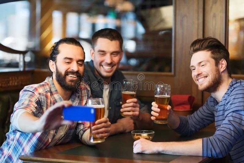 Amigos masculinos com cerveja bebendo do smartphone na barra foto de stock