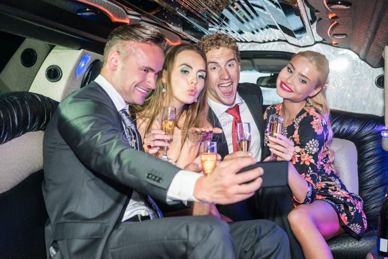 Amigos masculinos e fêmeas entusiasmado com as flautas de champanhe que tomam o sel fotografia de stock royalty free