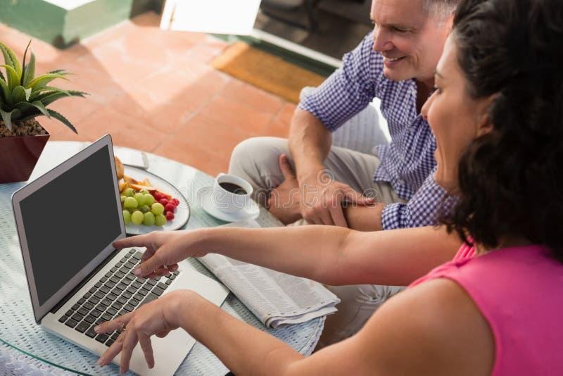 Amigos masculinos e fêmeas que discutem sobre o portátil no café exterior imagem de stock