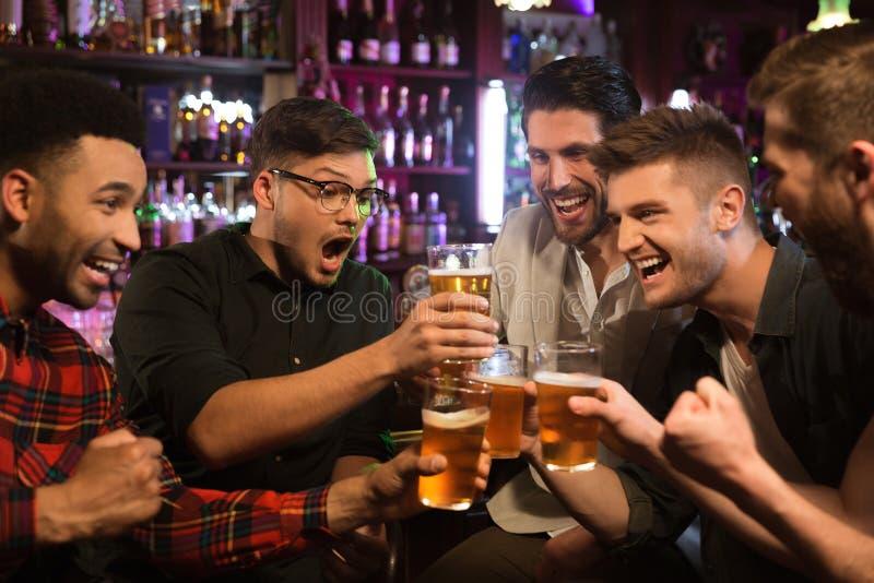 Amigos masculinos felices que tintinean con las tazas de cerveza en pub fotografía de archivo libre de regalías