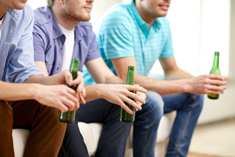Amigos masculinos felizes com cerveja que olham a tevê em casa imagens de stock royalty free