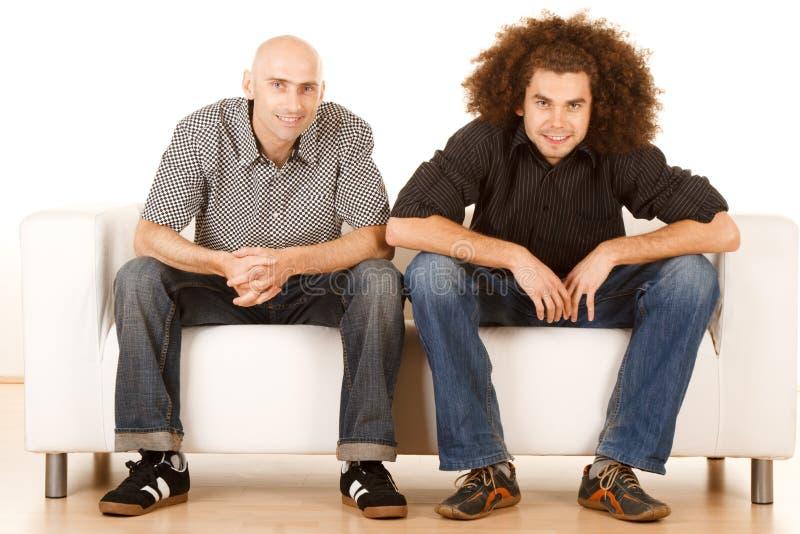 Amigos masculinos felizes do sofá imagens de stock royalty free