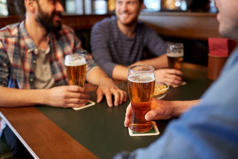 Amigos masculinos felizes que bebem a cerveja na barra ou no bar imagens de stock