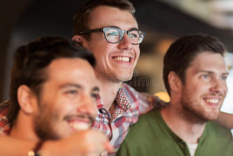 Amigos masculinos felizes que olham o futebol na barra ou no bar fotografia de stock royalty free