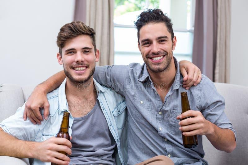 Amigos masculinos jovenes felices que gozan de la cerveza mientras que se sienta en el sofá fotografía de archivo libre de regalías