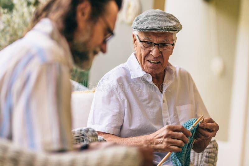 Amigos masculinos mayores kitting junto imagen de archivo libre de regalías