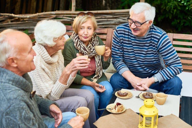 Amigos mayores en café imagenes de archivo