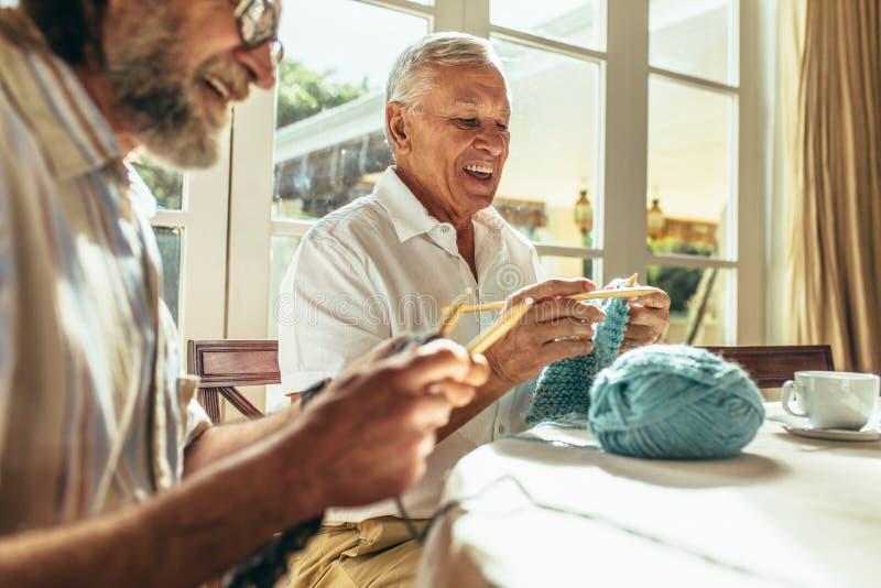 Amigos mayores que disfrutan de hacer punto en casa imágenes de archivo libres de regalías