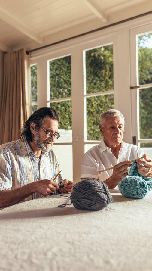 Amigos mayores que hacen punto en casa imágenes de archivo libres de regalías
