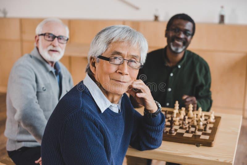 Amigos mayores que juegan a ajedrez fotografía de archivo