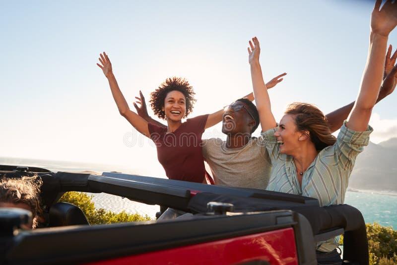 Amigos milenarios emocionados que viajan en la parte posterior de un coche abierto con sus brazos en el aire imágenes de archivo libres de regalías