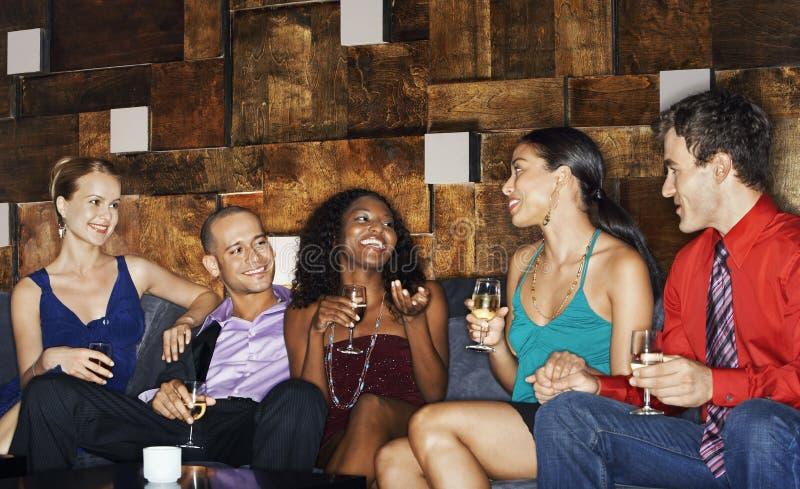 Amigos multiétnicos en el sofá con las bebidas foto de archivo libre de regalías
