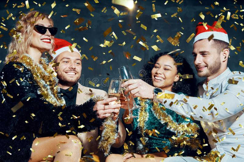 Amigos multiétnicos felizes a brindar com champanhe celebrando o Natal ou Ano Novo, felicitando-se uns aos outros e foto de stock