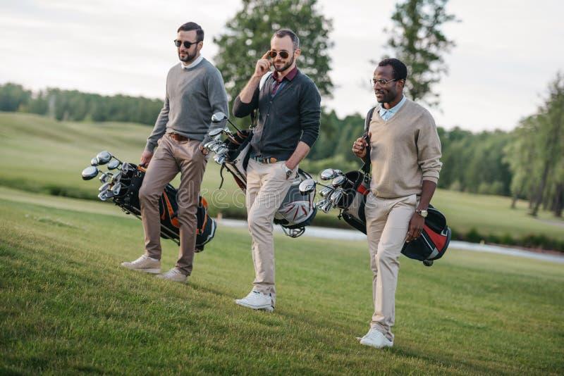 Amigos multiétnicos que sostienen bolsos con los clubs de golf y que caminan en campo de golf imagen de archivo libre de regalías
