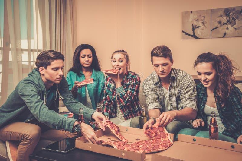 amigos Multi-étnicos con la pizza y las botellas de bebida imagen de archivo libre de regalías