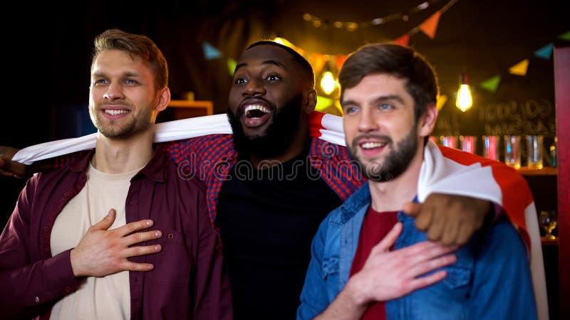Amigos multi-étnicos de sorriso envolvidos na bandeira inglesa que abraça, esporte de observação fotos de stock royalty free