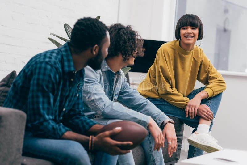 amigos multi-étnicos de sorriso novos que sentam-se no sofá com a bola para o futebol americano e que falam a cada um fotografia de stock