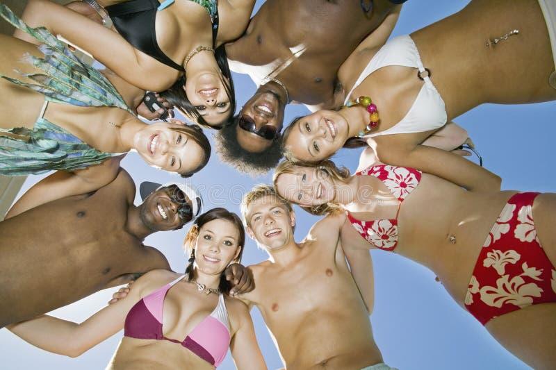 Amigos multi-étnicos novos que formam um círculo imagem de stock royalty free