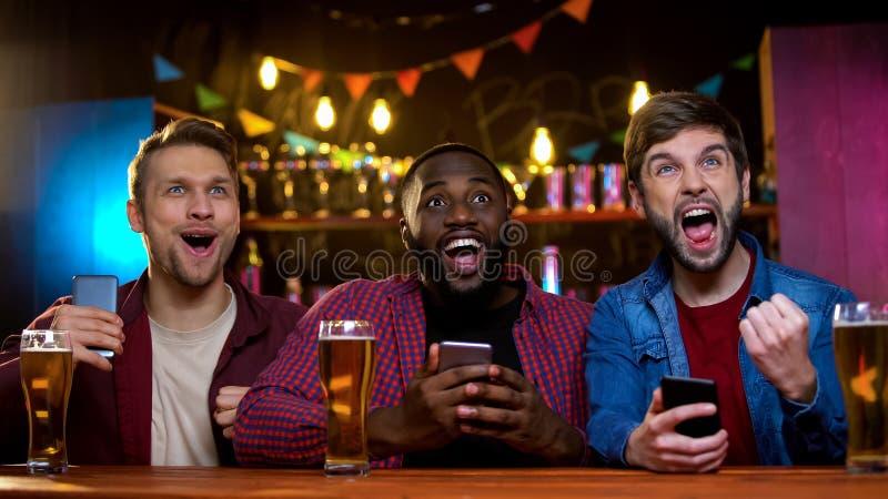 Amigos multi-étnicos que apoiam a equipe favorita, fazendo apostas para o resultado do jogo no bar imagens de stock